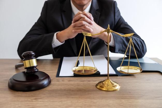Rechtsrecht, rat und gerechtigkeitskonzept, rechtsanwalt oder notar, die an dokumenten und bericht des wichtigen falls und des hölzernen hammers, messingskala auf tabelle im gerichtssaal arbeiten Premium Fotos
