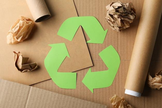 Recyceln sie zeichen auf handwerkshintergrund mit bastelpapier, draufsicht Premium Fotos