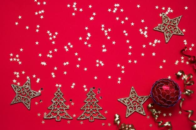 Red christmas hintergrund. weihnachtsverzierungen und goldene sterne auf hellem rotem hintergrund. Premium Fotos