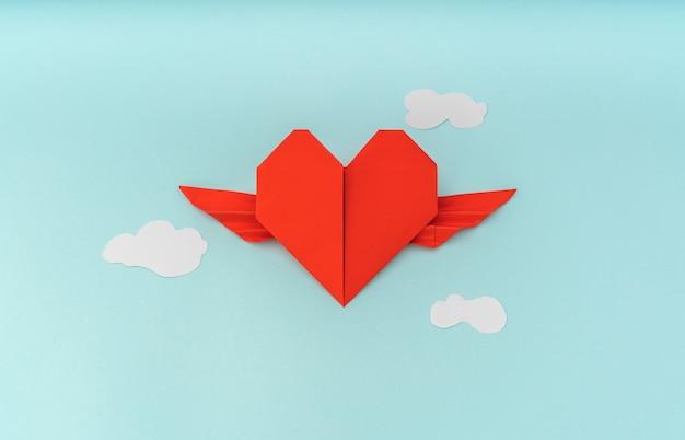 Red papier origami-herz mit flügeln und wolke auf blauem hintergrund Kostenlose Fotos