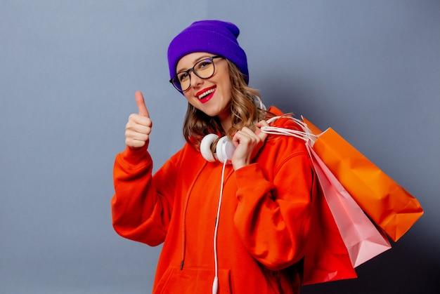 Reden sie mädchen im orange hoodie und im purpurroten hut mit einkaufstaschen auf grauer wand an Premium Fotos