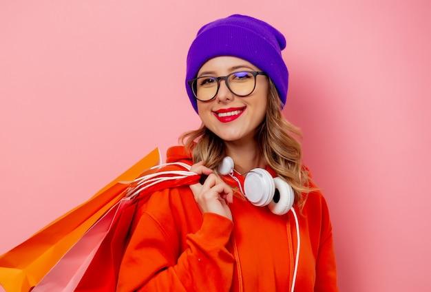 Reden sie mädchen im orange hoodie und im purpurroten hut mit einkaufstaschen auf rosa wand an Premium Fotos