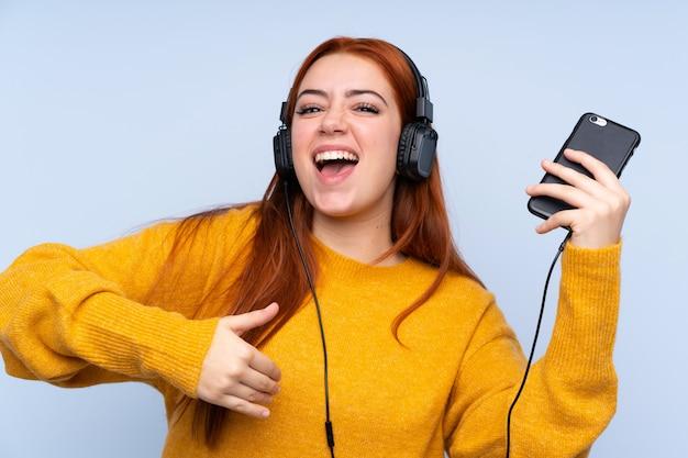 Redhead teenager-mädchen über blau musik hören und gitarrengeste tun Premium Fotos