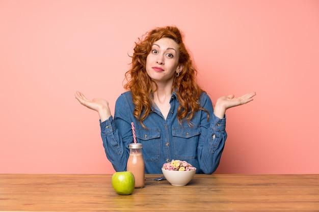 Redheadfrau, die frühstückskost aus getreide und frucht hat zweifel mit verwirren gesichtsausdruck hat Premium Fotos