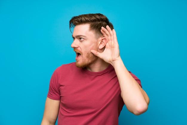 Redheadmann auf getrennter blauer hörender wand etwas Premium Fotos