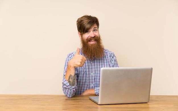 Redheadmann mit langem bart in einer tabelle mit einem laptop, der daumen gibt, up geste Premium Fotos