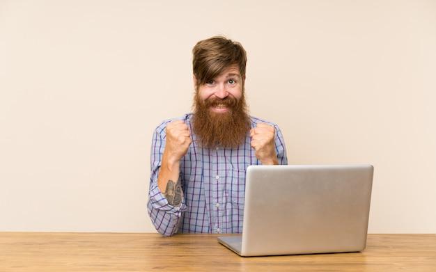 Redheadmann mit langem bart in einer tabelle mit einem laptop, der einen sieg feiert Premium Fotos