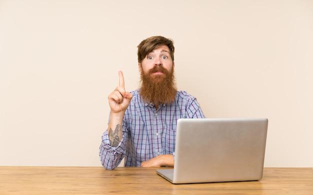 Redheadmann mit langem bart in einer tabelle mit einem laptop zeigend mit dem zeigefinger eine großartige idee Premium Fotos