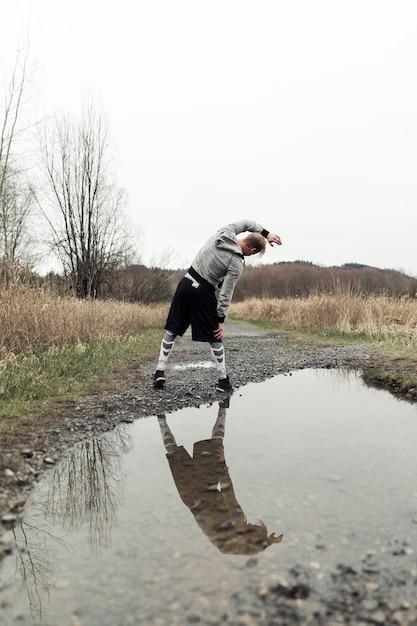 Reflexion des männlichen athleten beim pfützentrainieren Kostenlose Fotos