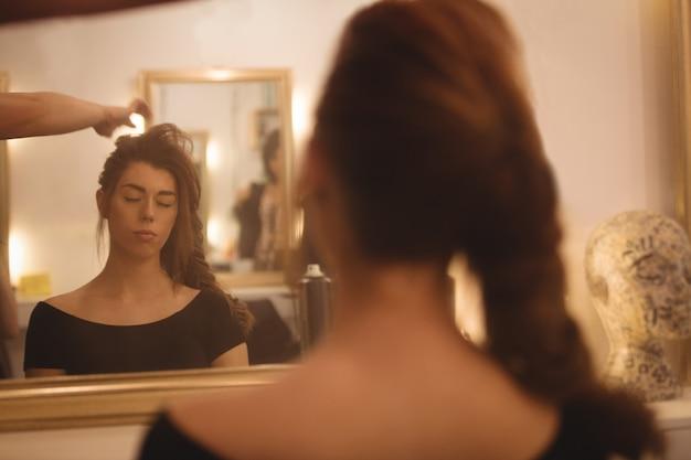 Reflexion einer frau auf dem spiegel, der ihr haar am saal anredet Kostenlose Fotos