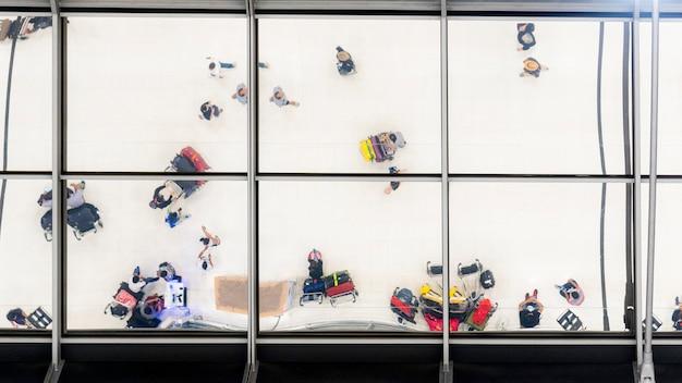 Reflexionsglas von draufsichtleuten gehen und sitzen in der bank mit gepäck und aktenkoffer, um am flughafen zu reisen Premium Fotos