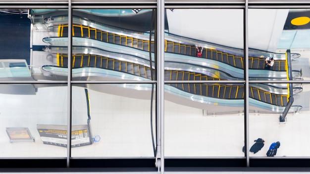Reflexionsglas von draufsichtleuten gehen und sitzen treppenrolltreppe am flughafen. Premium Fotos