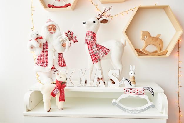 Regal mit weihnachtsfiguren weihnachtsmann und hirsch im kinderzimmer. weihnachtsinnenraum des kinderzimmers Premium Fotos