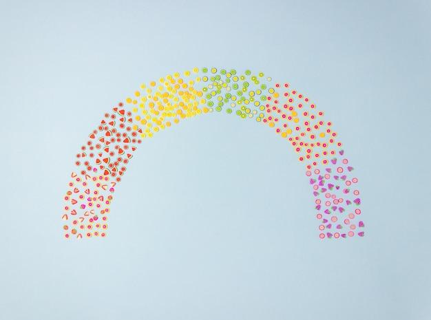 Regenbogen der spielzeugfrucht auf einem blauen hintergrund. minimales konzept. es ist eine kreative idee Premium Fotos