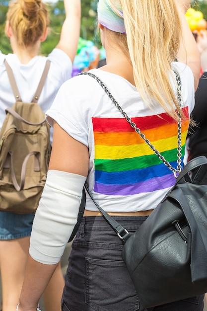 Regenbogen-lgbt-flagge auf rucksack der dame in der menge der leute auf prager stolz-parade Premium Fotos