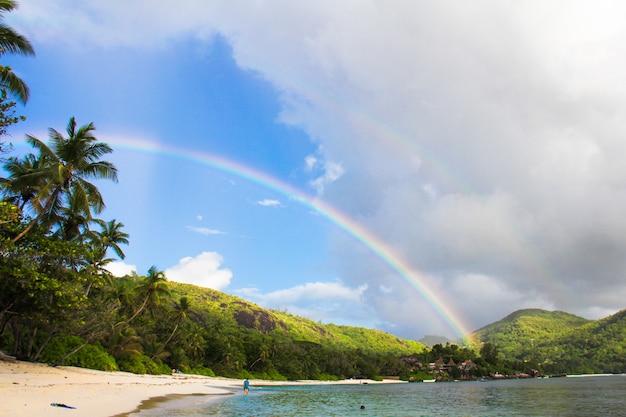 Regenbogen über tropischer insel und weißem strand bei seychellen Premium Fotos