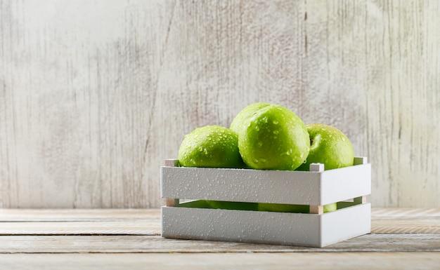 Regengrüne äpfel in einer holzkiste auf schmutz und hellem hölzernem hintergrund. Kostenlose Fotos