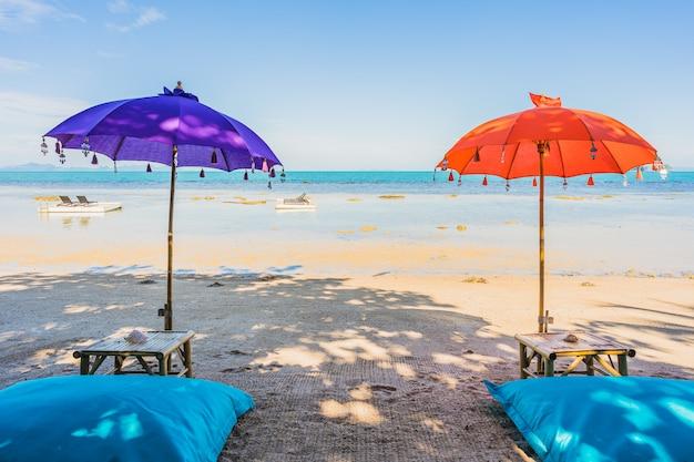 Regenschirm um schönen strandmeerozean für feiertagsferienreise Kostenlose Fotos
