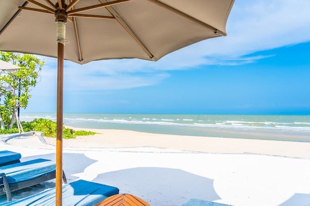 Regenschirm und stuhl auf dem strandseeozean mit blauem himmel und weißer wolke Kostenlose Fotos