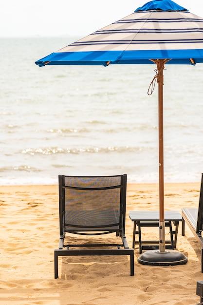 Regenschirm und stuhl um strandmeer mit blauem himmel Kostenlose Fotos