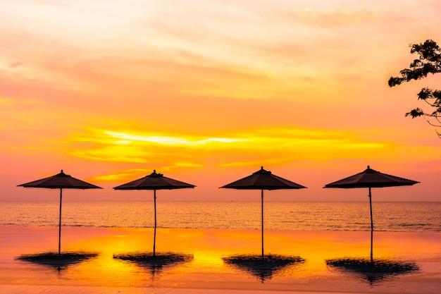 Regenschirm und stuhl um swimmingpool neary seeozean setzen zur sonnenaufgangs- oder sonnenuntergangzeit auf den strand Kostenlose Fotos