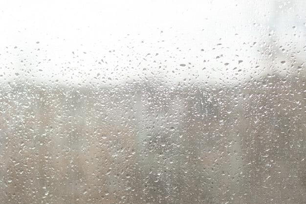 Regentropfen auf fensterglas tauchen mit bewölktem hintergrund auf Premium Fotos
