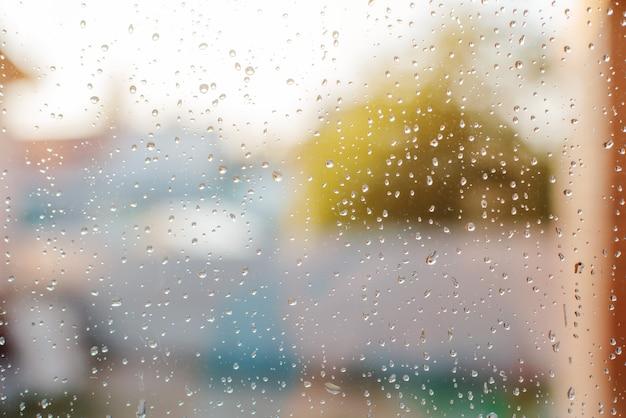 Regentropfen auf nassem fenster mit grünem baum und sonnenlicht im hintergrund, regnerischer tag des frühlinges. Premium Fotos