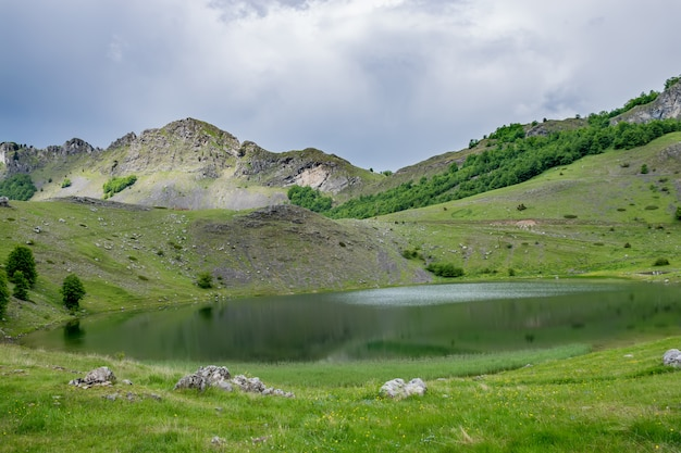 Regenwolken nähern sich dem bergsee. Premium Fotos