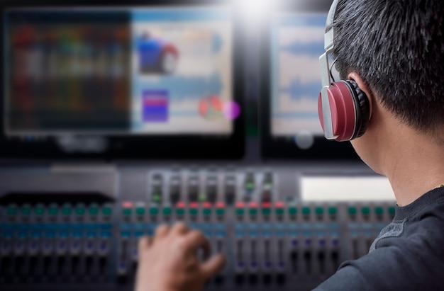 Regisseur mit kopfhörer arbeitet an video- und ton-mischkonsole im studio Premium Fotos