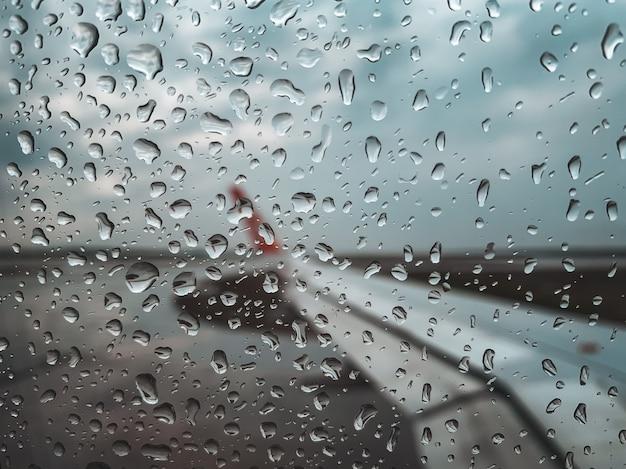 Regnen sie tropfen am flugzeugfenster, bevor sie wenn monsunjahreszeit sich entfernen. Premium Fotos