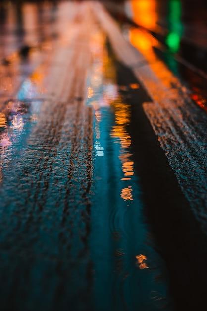 Regnerische nacht in einer großstadt, reflexionen von lichtern auf der nassen fahrbahn. Premium Fotos