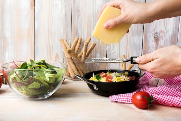 Reibender käse der hand der person über teigwaren in der küche Kostenlose Fotos