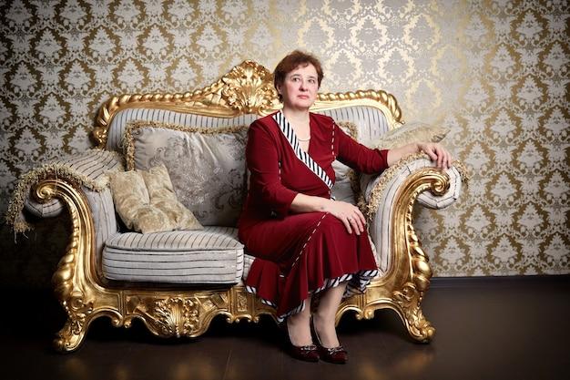 Reiche ältere frau, die auf einem teuren sofa sitzt Premium Fotos