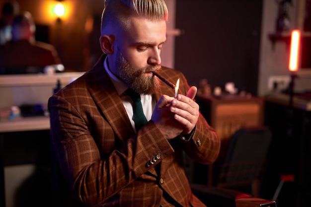 Reicher junger kaukasischer geschäftsmann im anzug rauchen eine zigarre, während er allein im dunklen raum sitzt Premium Fotos