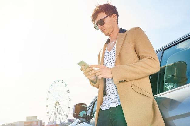 Reicher junger mann, der sich auf auto draußen stützt Premium Fotos