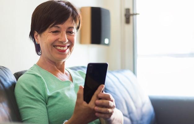 Reife ältere frau lächelnd mit smartphone sitzen auf dem sofa zu hause Premium Fotos