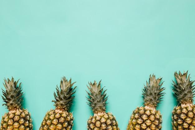 Reife ananas grenze rahmen auf türkis hintergrund isoliert. trendiges tropisches konzept des minimalistischen stils. leerer platz für text, kopie, beschriftung. Premium Fotos