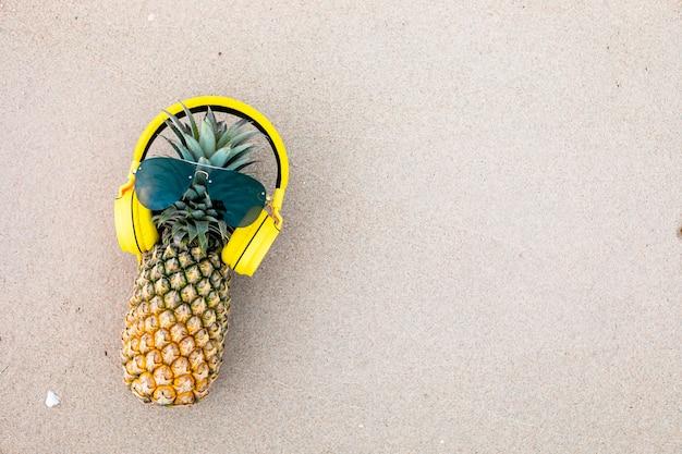 Reife attraktive ananas in stilvoller verspiegelter sonnenbrille und goldenen kopfhörern auf sand gegen türkisfarbenes meerwasser. tropisches sommerferienkonzept. Premium Fotos