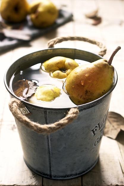 Reife birnen und birnenblätter in einem eiseneimer mit wasser und auf einem holztisch. rustikaler stil. Premium Fotos
