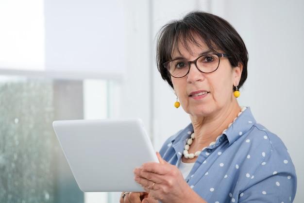 Reife brunettefrau, die auf sofa unter verwendung der digitalen tablette sitzt Premium Fotos
