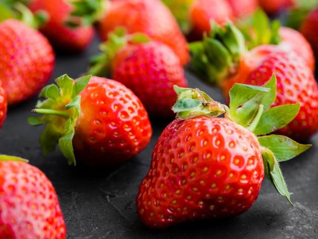 Reife erdbeere auf schwarzer oberfläche Kostenlose Fotos