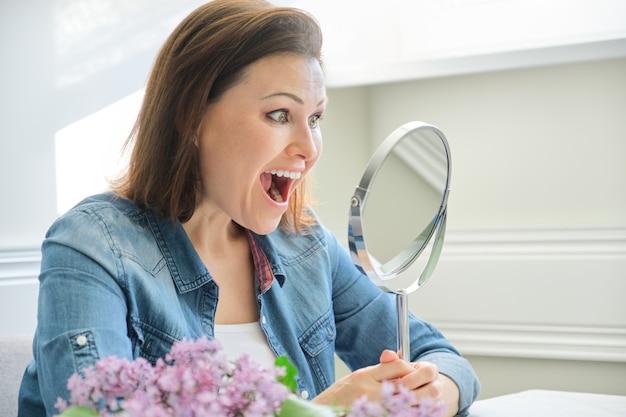 Reife frau, die in den spiegel schaut und schreit Premium Fotos