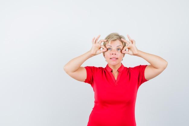 Reife frau, die ok zeichen nahe augen im roten t-shirt zeigt Kostenlose Fotos