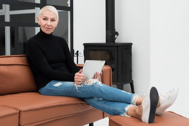 Reife frau, die tablette hält und auf dem sofa sich entspannt Kostenlose Fotos