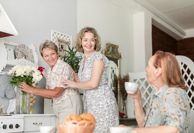 Reife frau mit der tochter, die blumenvase auf küchenarbeitsplatte während ihre mutter trinkt kaffee vereinbart Kostenlose Fotos