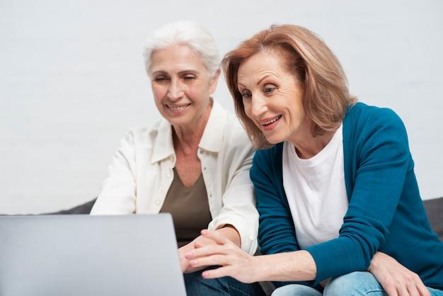 Reife frauen, die auf einem laptop grasen Kostenlose Fotos