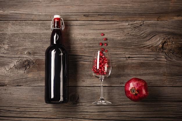 Reife granatapfelfrucht mit einem glas wein, eine flasche auf einem hölzernen hintergrund Premium Fotos