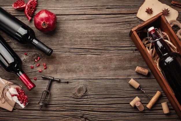 Reife granatapfelfrucht mit einem glas wein, eine flasche in einem kasten auf einem hölzernen hintergrund Premium Fotos