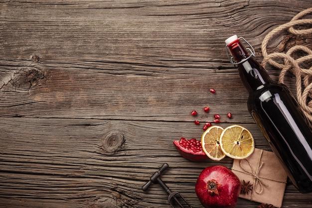 Reife granatapfelfrucht mit einem glas wein, einer flasche und einem korkenzieher auf einem hölzernen hintergrund Premium Fotos