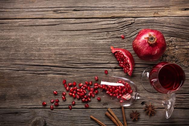 Reife granatapfelfrucht mit einem glas wein und einem korkenzieher auf einem hölzernen hintergrund Premium Fotos